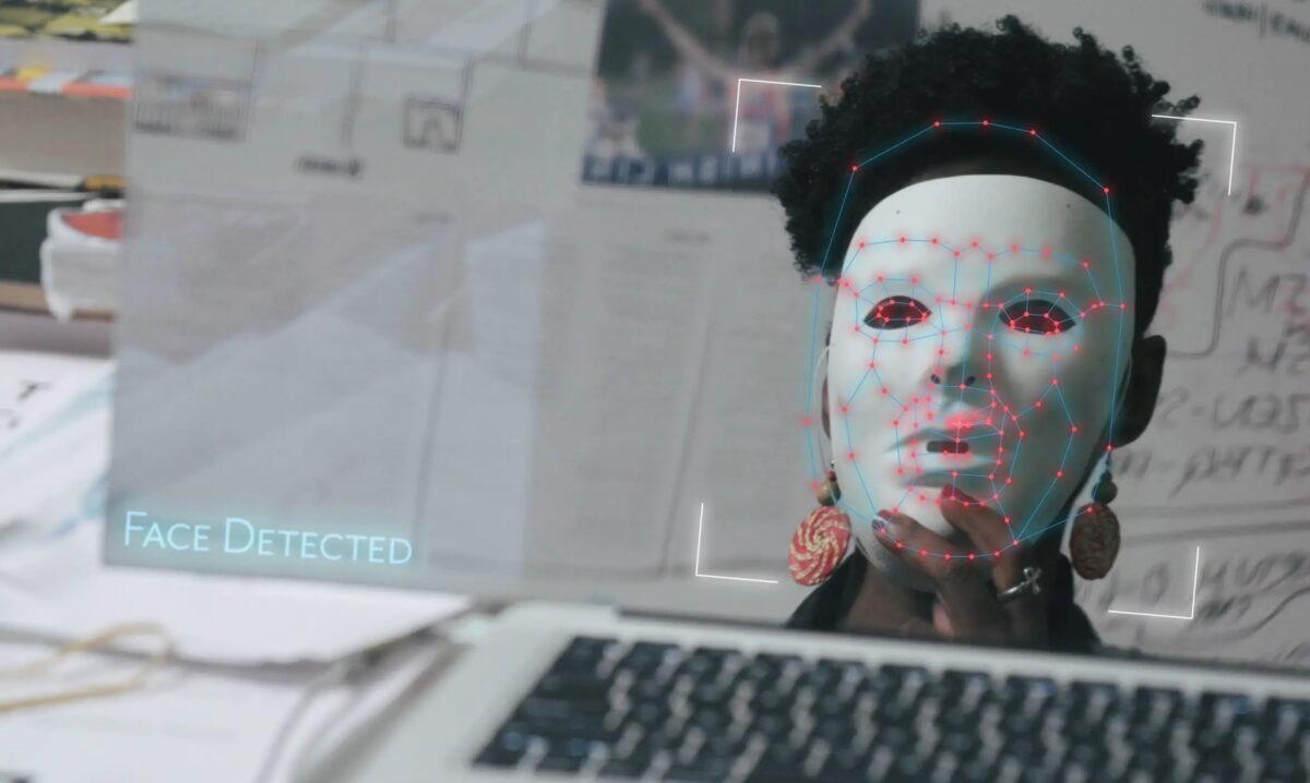 Eine Schwarze Frau sitzt vor einem Laptop und hält sich eine weiße Theater-Maske vor das Gesicht. Auf dem Bildschirm steht: Face Detected.
