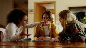 Zada, Julija und Caro sitzen am Tisch und diskutieren über das Buch.