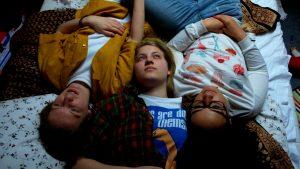 Julija, Caro und Zada liegen Kopf an Kopf zu dritt auf dem Bett