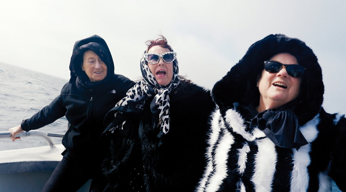 An der Reling eines Bootes stehen drei ältere Personen, eine komplett in schwarz gekleidet, und zwei Frauen mit extravaganter schwarz-weißer Kleidung. Im Hintergrund ist Wasser.