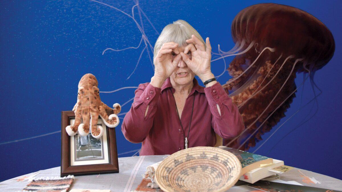 Eine Frau mit grauen Haaren und roter Bluse sitzt vor einem blauen Hintergrund. Sie hält ihre Hände in O-Form vor ihre Augen. Auf dem Tisch vor ihr stehen ein Bild, auf dem ein Plüsch-Oktopus sitzt, und eine Navajo-Strohschale. Im Hintergrund ist außerdem ein weiterer, grpßer Oktopus zu sehen.