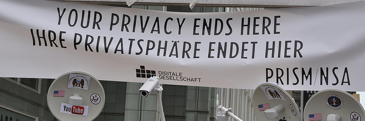 """Am Checkpoint Charlie ein weißes Plakat mit schwarzer Schrift: """"Your privacy ends here - Ihre Privatsphäre endet hier"""" und kleine Videokameras und Audioüberwachungsgeräte"""