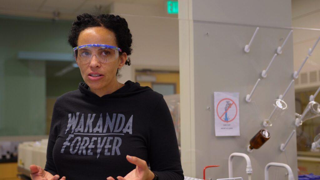 In einem Chemielabor steht eine schwarze Frau mit Schutzbrille. Auf ihrem schwarzen Kapuzenpullover ist die Aufschrift: Wakanda Forever.