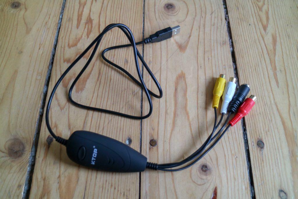 Ein schwarzer Kasten mit einem USB-Anschluss auf der einen Seite und vier runden Anschlüssen auf der anderen Seite