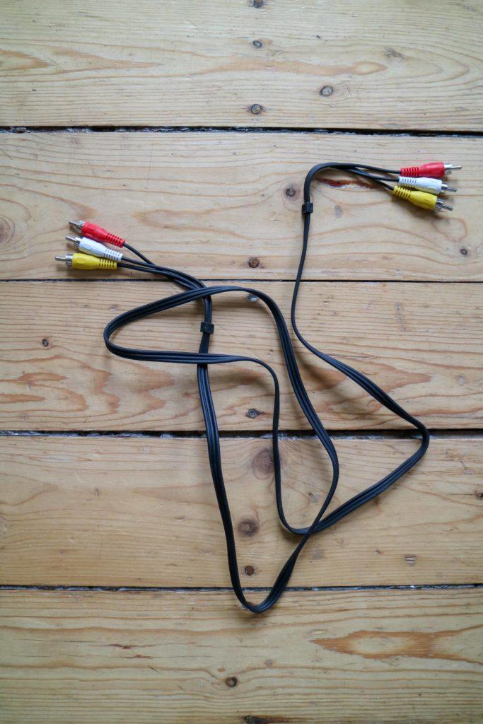 Ein schwarzes Kabel mit jeweils drei bunten Steckern an beiden Seiten (rot, weiß und gelb)