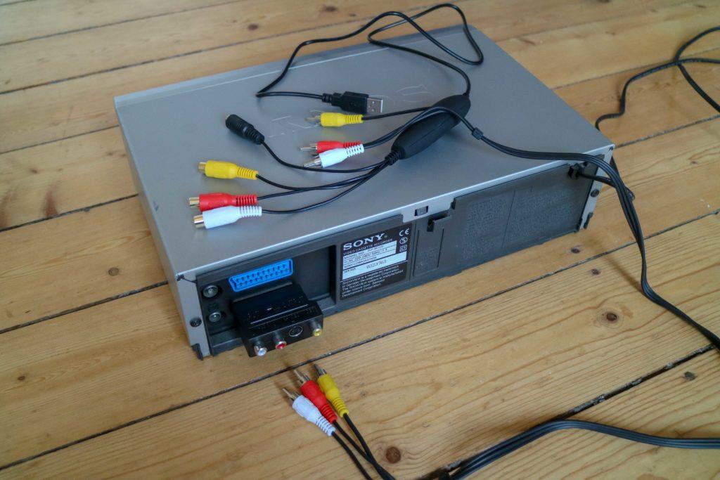 Ein Videorekorder, auf und neben dem Cinch-Kabel und der USB-Audio-Video-Grabber liegen