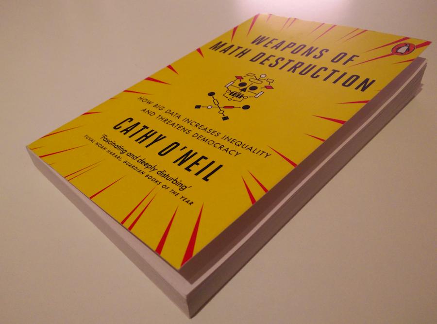 Das Buch Weapons of Math Destruction der Autorin Cathy O'Neil mit gelbem Cover mit roten Zacken und Totenkopfsymbol auf einem weißen Tisch