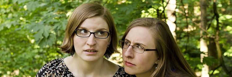 Zwei junge weiße Frauen mit dunkelblonden Haaren stehen im Wald und horchen und gucken skeptisch.