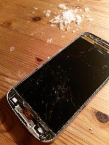 Smartphone ohne vorderste Glasscheibe, daneben ein Haufen Klebstoff-Krümel