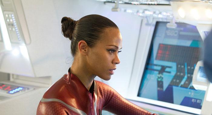 Eine schwarze Frau im roten Kleid sitzt vor einer Computerkonsole