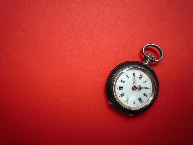 Roter Hintergrund, darauf ist eine altmodische Uhr zum Aufziehen.