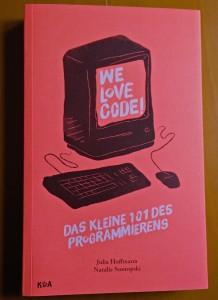 Die Titelseite von We Love Code! zeigt die Illustration eines Computers mit Maus und Tastatur in Schwarz. Der Hintergrund ist in neonorange gestaltet.