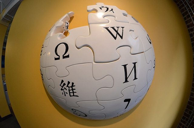 Ein weißer Puzzleball mit W, Omega und weiteren Symbolen für die Wikipedia. In einem fehlenden Puzzleteil steht ein Mini-Stormtrooper.