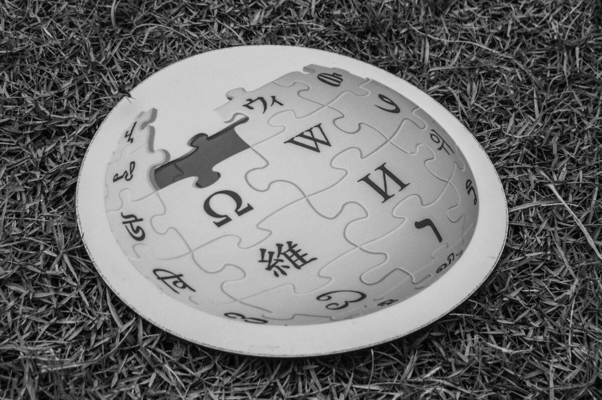 Auf einem grauen Hintergrund liegt ein rundes Mauspad mit Wikipedia-Logo.